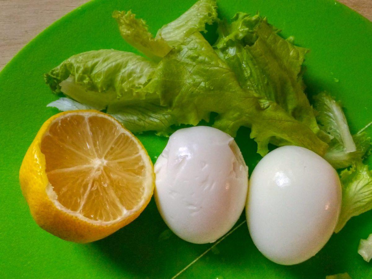 Листья салата, лимон, вареные куриные яйца